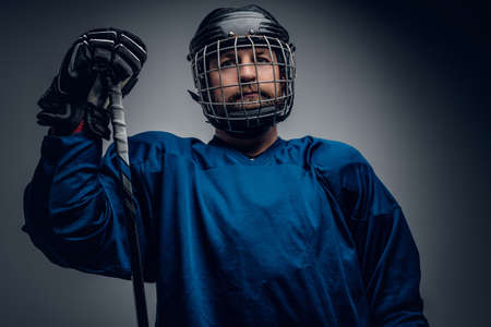 icehockey: A brutal bearded ice-hockey player in safety helmet holds the gaming stick on grey vignette background.