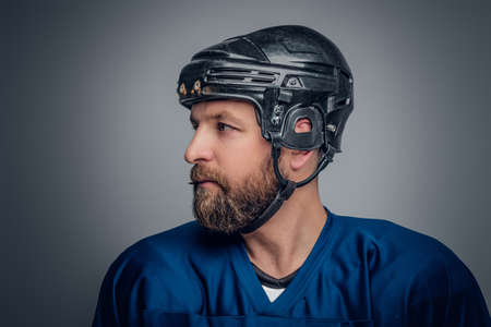 icehockey: Close up portrait of ice-hockey player in safety helmet on grey vignette background.