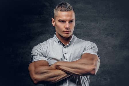 male fashion model: Sporty young male with crossed muscular arms, dressed in a white shirt isolated on grey vignette background. Stock Photo