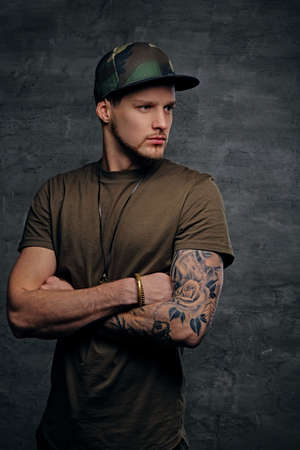 Young stylish male with tattooed arm dressed in khaki t shirt and a military cap.