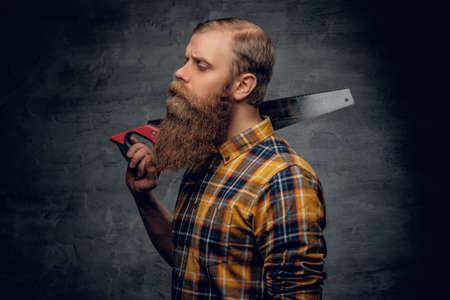 serrucho: Studio portrait of bearded carpenter dressed in a plaid shirt holds handsaw on grey vignette background. Foto de archivo