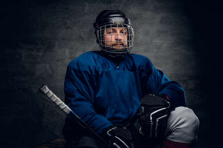 icehockey: A bearded ice-hockey player in a blue sportswear holds a gaming stick in contrast illumination on grey vignette background.
