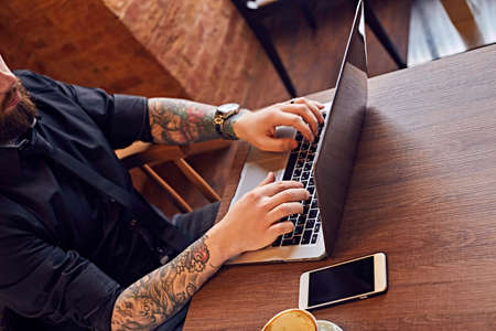 Close up image of hipster male with tattooed arms working with a laptop.