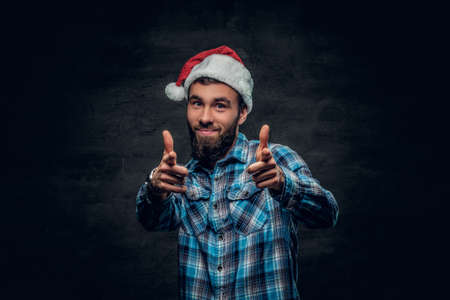 Studio portrait of bearded male dressed in a plaid shirt and Santas hat isolated on grey vignette background.