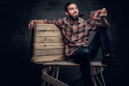 serrucho: Retrato de vestidos masculinos carpintero con barba en una camisa a cuadros y pantalones vaqueros sostiene sierra de mano en un hombro.
