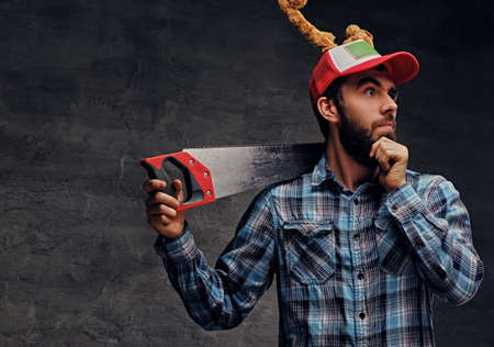plaid shirt: Portrait of bearded male dressed in a plaid shirt and a hat with Christmas deers horns holds handsaw on a shoulder.