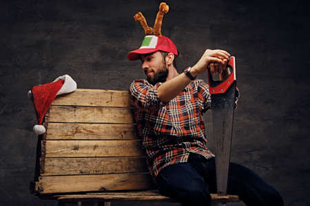 Christmas scene studio portrait of bearded male in holiday hat with deers horns holds handsaw.