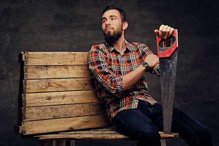 Studio portrait of bearded carpenter male dressed in a jeans and a plaid shirt sits on a wooden palette and holds handsaw.