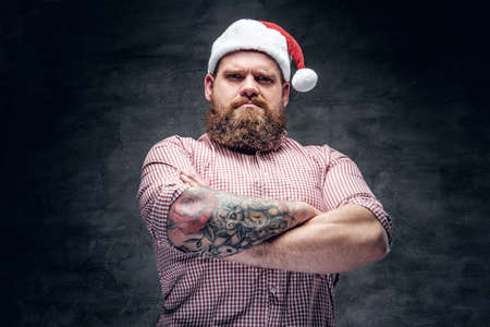 Brutal bearded male with tattooed arm wearing Santas New Year hat.