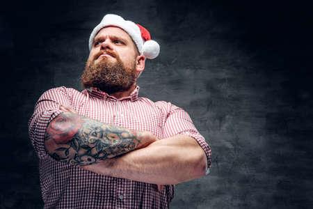 Brutale bebaarde man met een getatoeëerde arm die Santa's nieuwjaarshoed draagt. Stockfoto