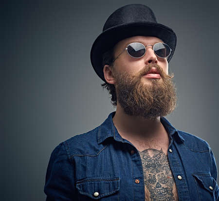 Studio portrait of stylish bearded male with a tattoo on his chest, dressed in a denim shirt, cylinder hat and sunglasses isolated on grey background. Stock Photo