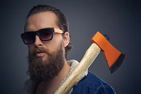 Portrait of bearded male in sunglasses with a tattoo on his chest wearing a denim jacket and holds axe over grey background.