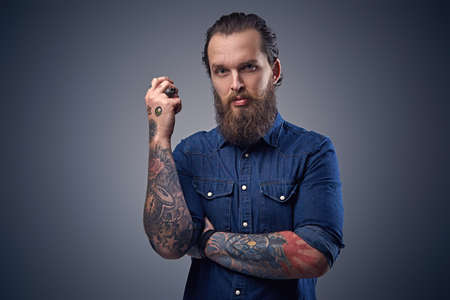 uniformity: Bearded male with tattoos on arms, dressed in denim shirt over grey background.