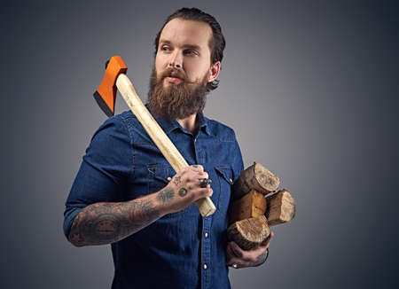 uniformity: Bearded male with tattoos on arms wearing a denim shirt holds an axe and firewoods over grey background.