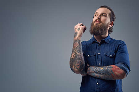 Bearded male with tattoos on arms, dressed in denim shirt over grey background.