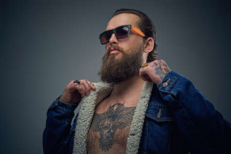 uniformity: Portrait of bearded male in sunglasses with tattoo on a chest wearing a denim jacket.