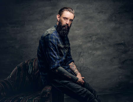 lumberjack shirt: Portrait of bearded male with tattooed arms, dressed in a plaid flannel shirt sits on a chair over dark grey background.
