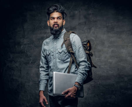 uniformity: The Indian male student holds laptop and backpack over grey studio background.