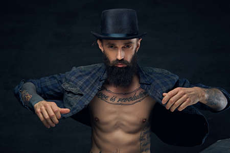 lumberjack shirt: Bearded male in top hat with tattoos on his chest over dark background. Stock Photo