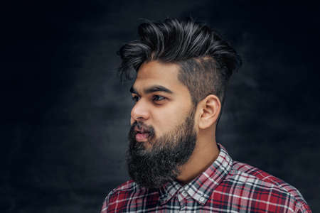 uniformity: Attractive bearded Indian man in plaid fleece shirt over grey background.