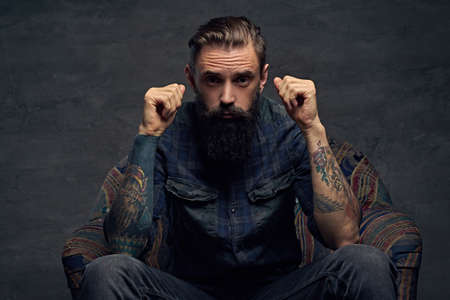 uniformity: Portrait of bearded male with tattooed arms, dressed in a plaid flannel shirt sits on a chair over dark grey background.