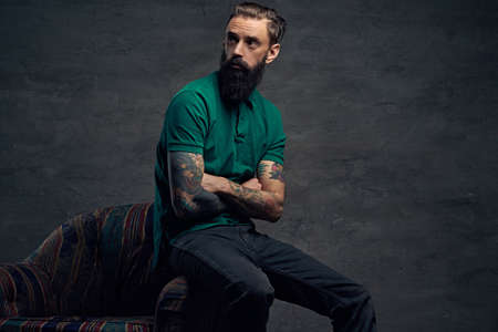 Bearded male with crossed tattooed arms, dressed in a green t shirt sits on a chair over grey background. Stock Photo