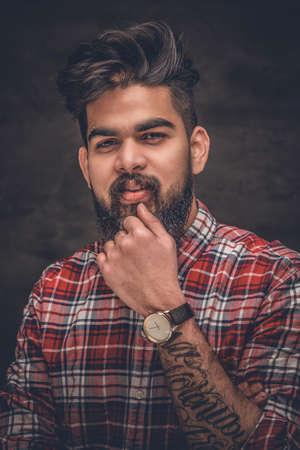 Atraktivní vousatý Indický muž v kostkované košili fleece na šedém pozadí.