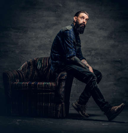 Full body portrait of tattooed, bearded male dressed in a plaid flannel shirt sits on a chair over dark grey background. Reklamní fotografie