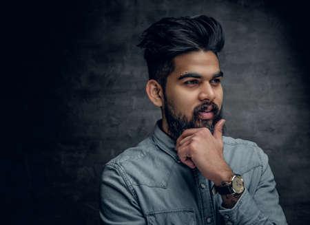 lumberjack shirt: Portrait of stylish bearded Indian male dressed in a denim jacket. Stock Photo
