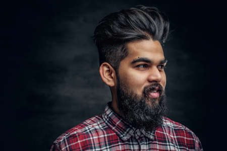 Attractive bearded Indian man in plaid fleece shirt over grey background.