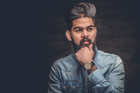 uniformity: Studio portrait of stylish bearded Indian man in a blue shirt over grey background.