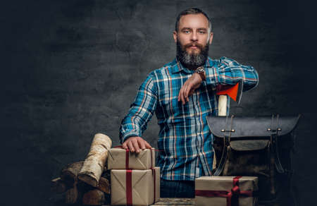 uniformity: Portrait of bearded middle age male holds an axe and standing near a table with Christmas gift boxes and firewoods over grey background.
