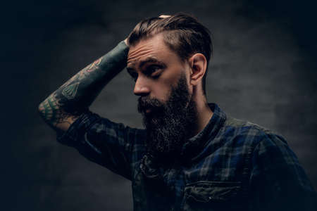 uniformity: Bearded male with tattoo on arm touches his head.