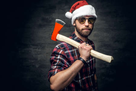 Portrait of a bearded man wearing Santas hat and holds axe.