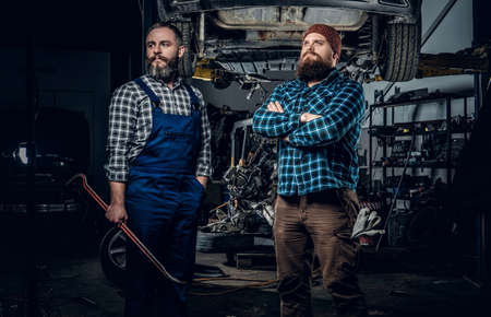 uniformity: Two brutal bearded mechanics repairing a car in a garage. Stock Photo
