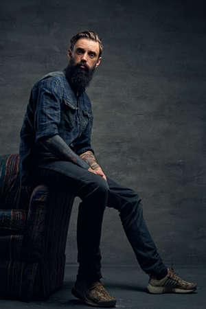 Celé tělo portrét tetovaný, vousatý samec oblečená v kostkované flanelové košili sedí na židli přes tmavě šedém pozadí.
