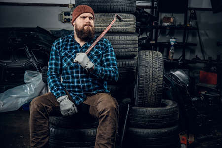Bearded mechanic sits on an old cars tire in a garage.
