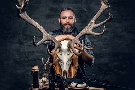 hunter man: Portrait of hunter man holds a deers skull. Stock Photo