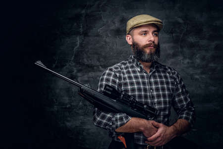 Studio portrait of bearded hunter male wearing a plaid fleece shirt holds a rifle. Stock Photo