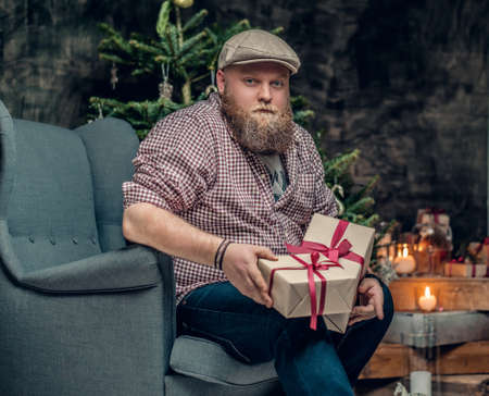 uniformity: The fat bearded male sits on a chair with a Christmas fir tree in background.