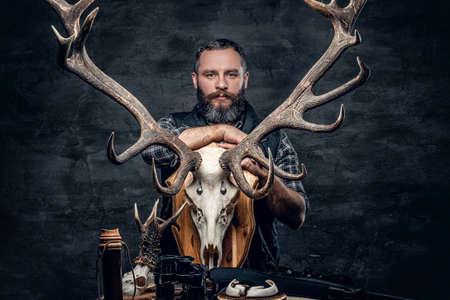 Portrait of hunter man holds a deers skull. Stock Photo