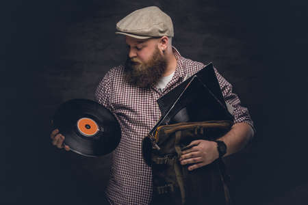 uniformity: Fat bearded hipster man holds vinyl records.