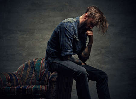 Stylish hipster male posing on a chair over grey background. Stock Photo