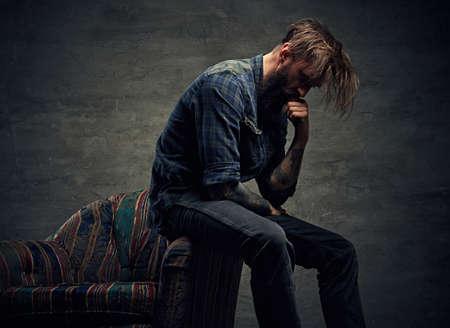 Stylový hipster muž lodě na židli na šedém pozadí. Reklamní fotografie