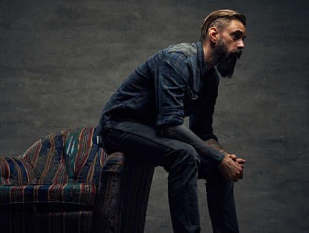 uniformity: Stylish hipster male posing on a chair over grey background. Stock Photo