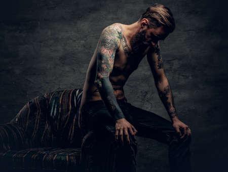 회색 배경 위에 shirtless, 문신 수염 난된 남성 앉아의 자에.