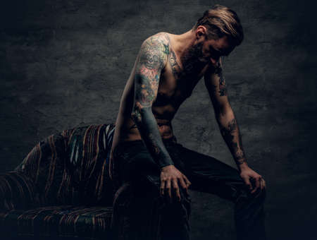 The shirtless, tattooed bearded male sits on a chair over grey background. Archivio Fotografico