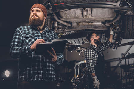 uniformity: Bearded mechanics male inspecting cars engine in a garage.
