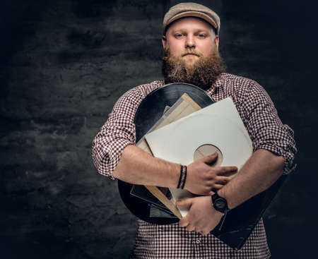 Fat bearded hipster man holds vinyl records.