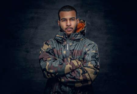Studio portret van een zwarte man, gekleed in militaire jas. Stockfoto